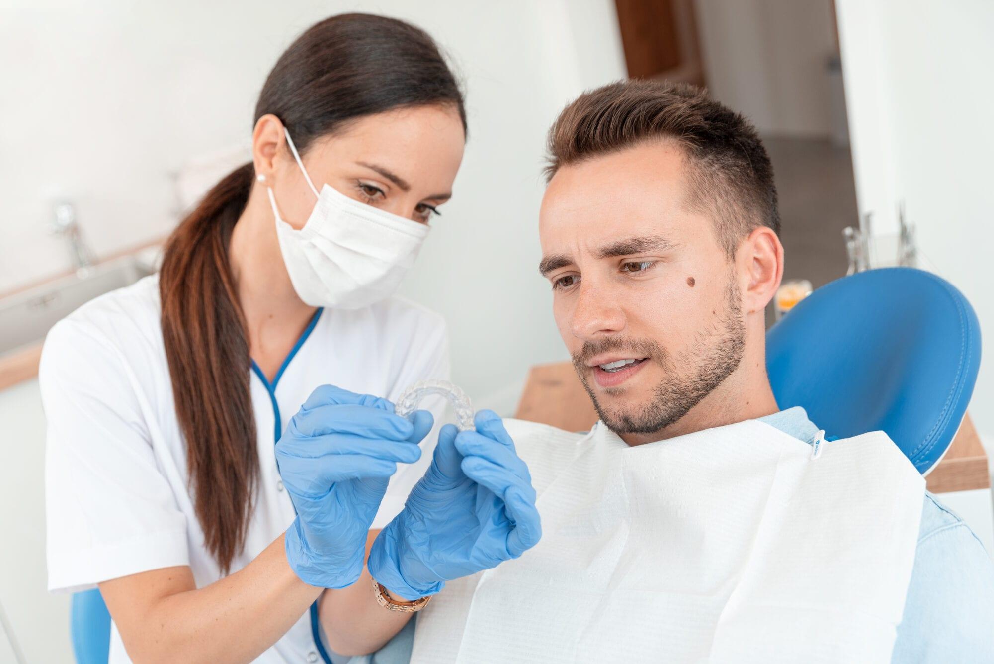 Dentist shows invisible braces aligner